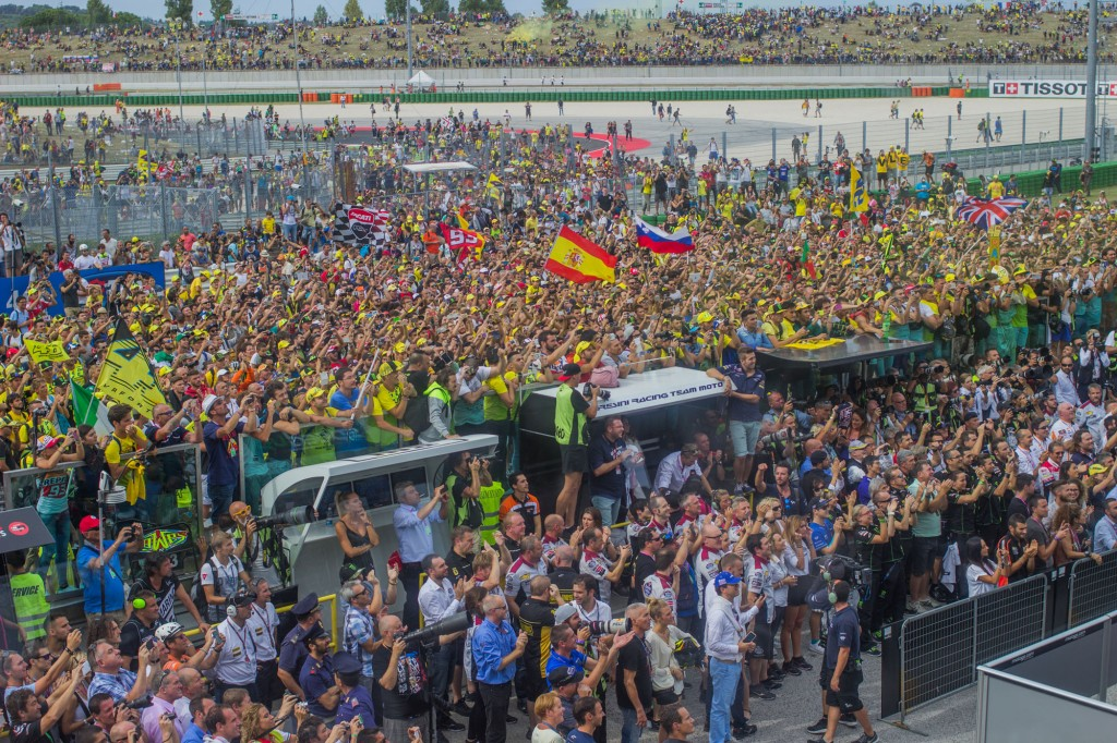 The yellow crowd is not satisfied with the podium result. They call the name of their hero, and Rossi is rushed in front of them in order to say hello to his fans.