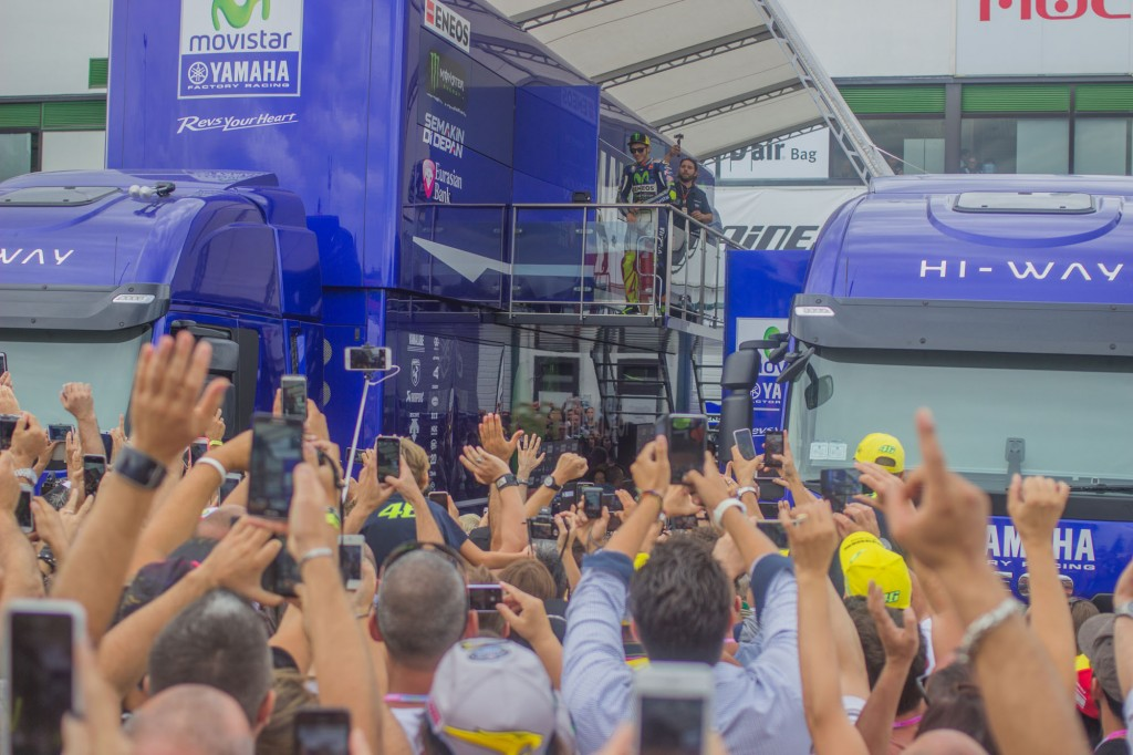 "I leave Antonelli and his crew to the setting of the Moto3 Honda and head towards the central part of the paddock. But my way is blocked by a crowd of people waiting for something, or somebody. ""Is he there?"", I hear someone saying. ""Is he coming?"", a young boy dressed in a yellow cap and t shirt asks his father. Then Valentino Rossi appears, and people start to yell. He's entering the Yamaha truck and cheers at the crowd. Smart phones up, mouths open, voices loud. ""Vale, Vale, Vale"", the people say in a soccer-stadium-style. When Rossi is out of the view half of the pack leaves, while the other half remains there, waiting for him to exit the truck."