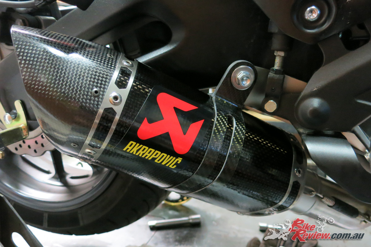 You can get the carbon-fibre exhaust hanger into place by gently stretching it out so it won't scratch the muffler.