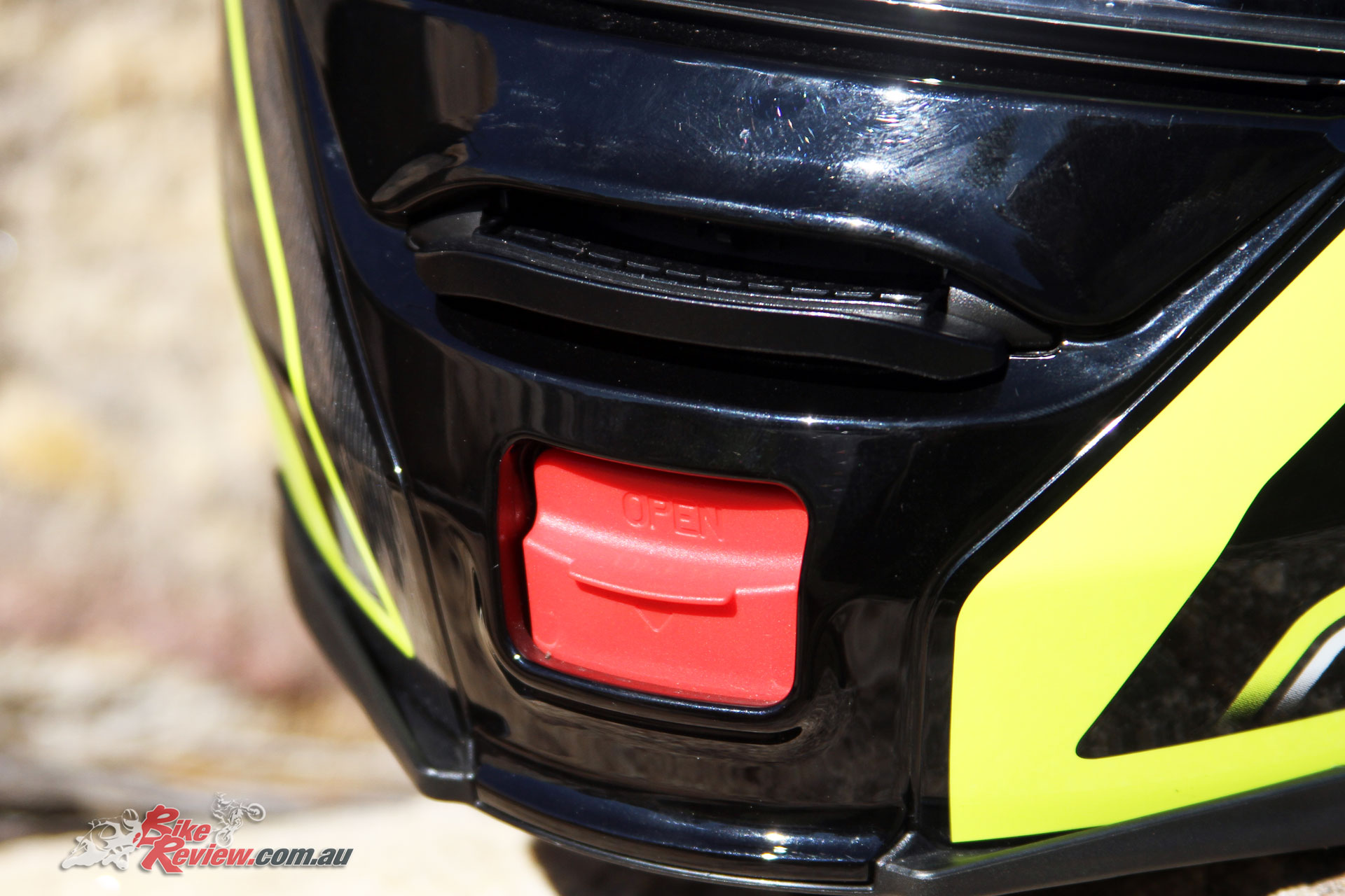 The modular flip up button and chin vent on the Shoei Neotec II.