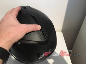 The sun visor lever is located on the top of the helmet.